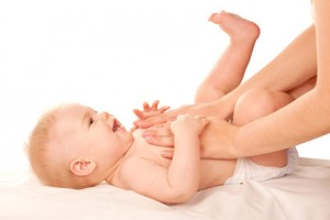 Baby massage. Mother massaging kid belly, baby laughing.